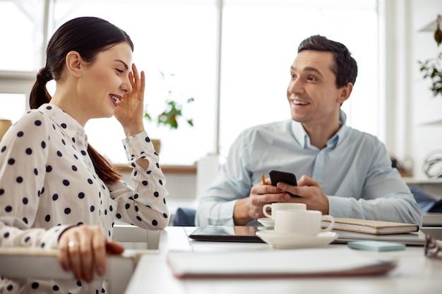 Przyjazna atmosfera. przystojny, wesoły ciemnowłosy mężczyzna, uśmiechając się i trzymając swój telefon i jego koleżanka siedząca obok niego i rozmawiają