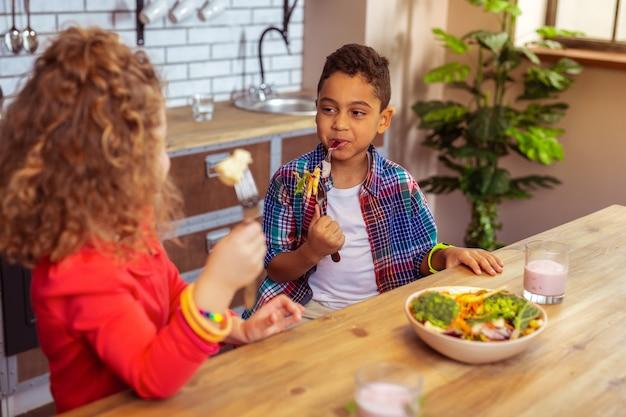 Przyjazna atmosfera. radosny ciemnoskóry dzieciak patrzący na swojego przyjaciela podczas wspólnego obiadu