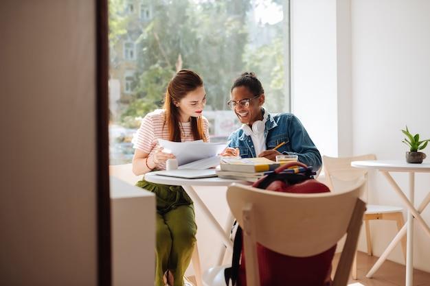 Przyjazna atmosfera. śliczna brunetka dziewczyna trzyma kartki papieru podczas sprawdzania zadania domowego