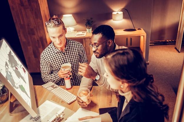 Przyjazna atmosfera. zadowolony ciemnoskóry mężczyzna siedzi między kolegami, omawiając pracę nad projektem
