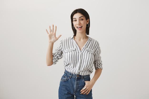 Przyjazna atrakcyjna dziewczyna macha ręką, aby się przywitać, witając gości