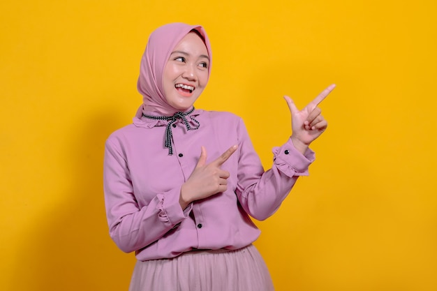 Przyjazna, atrakcyjna dziewczyna wskazująca prawy palec wskazujący, uśmiechająca się szeroko, pewna siebie, zrelaksowana