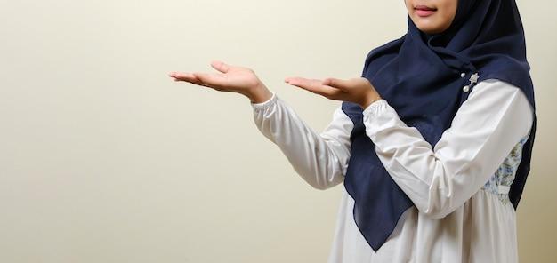 Przyjazna azjatycka muzułmańska dziewczyna pokazująca coś u boku obiema rękami, odizolowana na białym tle