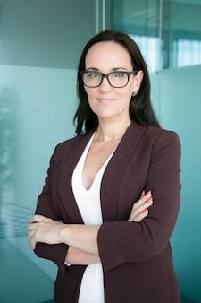 Przyjazna biznesowa pani w formalnym garniturze i okularach, stojąca z założonymi rękoma i uśmiechnięta