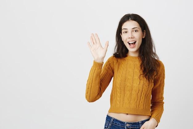 Przyjazna brunetka dziewczyna mówi cześć, macha ręką na cześć, miło cię poznać gest