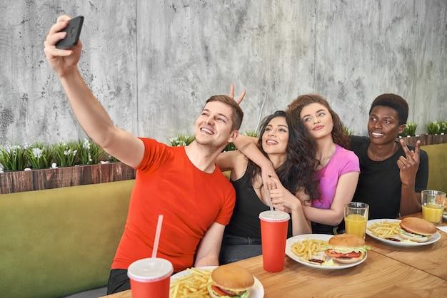 Przyjazna firma robi selfie w kawiarni podczas lunchu