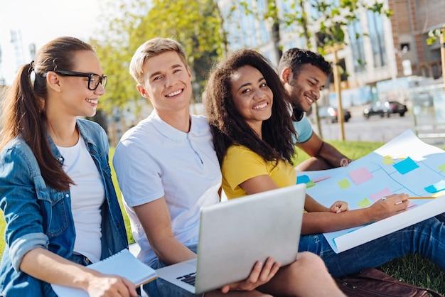 Przyjazna grupa. zachwyceni uczniowie wyrażający pozytywne nastawienie podczas wspólnej pracy i spędzania przerwy na świeżym powietrzu