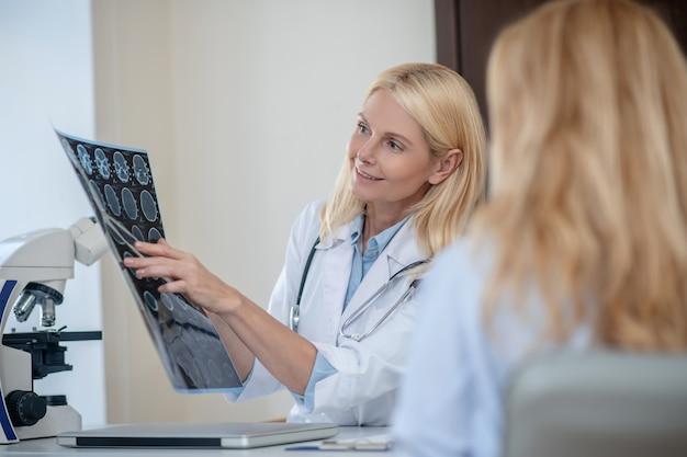 Przyjazna, ładna kobieta lekarz rozszyfrowuje skan mrt przedstawiający pacjenta siedzącego w gabinecie