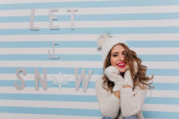 Przyjazna, miła młoda dziewczyna z piękną, jasną szminką, uśmiechająca się słodko, dotykająca twarzy dłońmi w rękawiczkach. portret pozowanie uśmiechnięty model z lokami siedzącymi przed pasiastą niebieską ścianą