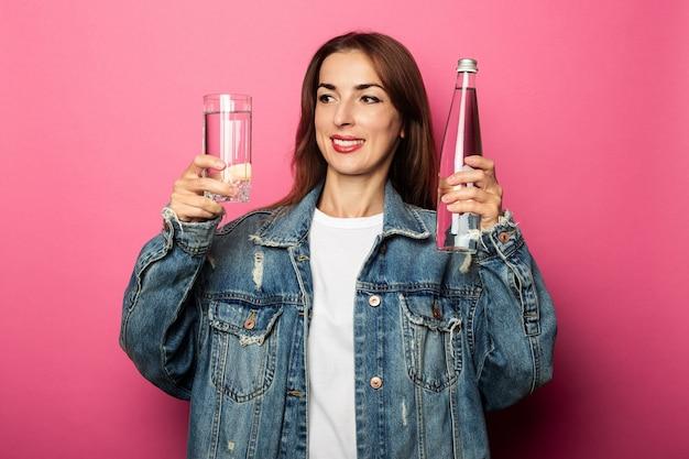 Przyjazna młoda kobieta trzyma butelkę wody, patrząc na szklankę wody