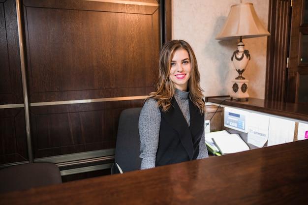 Przyjazna młoda kobieta za administratorem recepcji