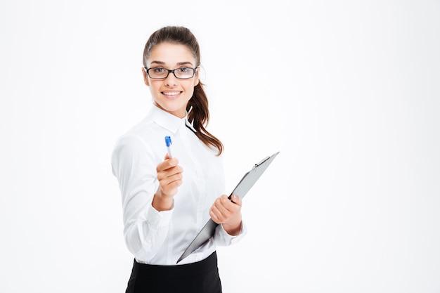 Przyjazna młoda uśmiechnięta bizneswoman ze schowkiem wskazującym pióro z przodu na białym tle na białej ścianie
