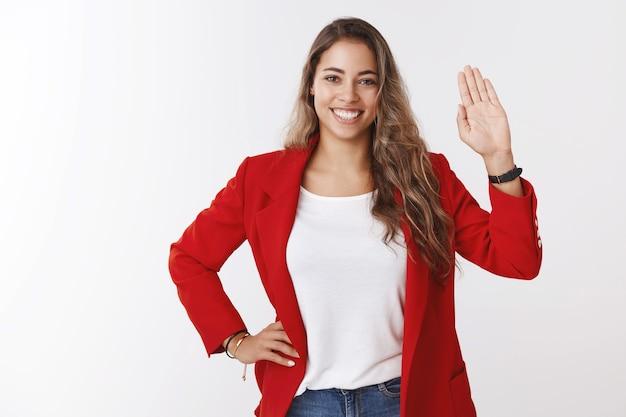 """Przyjazna, pewna siebie, atrakcyjna młoda europejska kobieta z kręconymi włosami w wieku 25 lat ubrana w czerwoną kurtkę machająca podniesioną dłonią cześć powitalny gest uśmiechnięta, pozdrawiająca członków zespołu, mówiąca """"cześć poznawanie nowych ludzi"""""""
