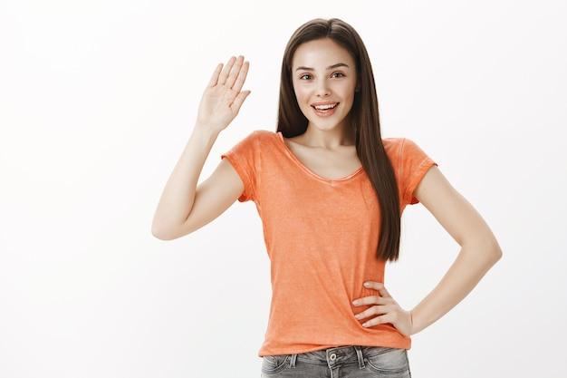 Przyjazna piękna młoda dziewczyna mówi cześć, macha ręką gest powitania, witamy osobę