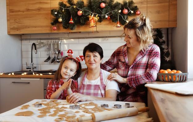 Przyjazna rodzina gotuje imbirowe ciasteczka w kuchni i wesoło się śmieje