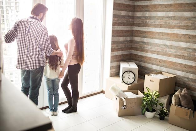 Przyjazna rodzina stoi przy oknie i wygląda na zewnątrz. po prawej stronie mieszkania znajdują się pudła dla mężczyzn. ludzie mówią o czymś.