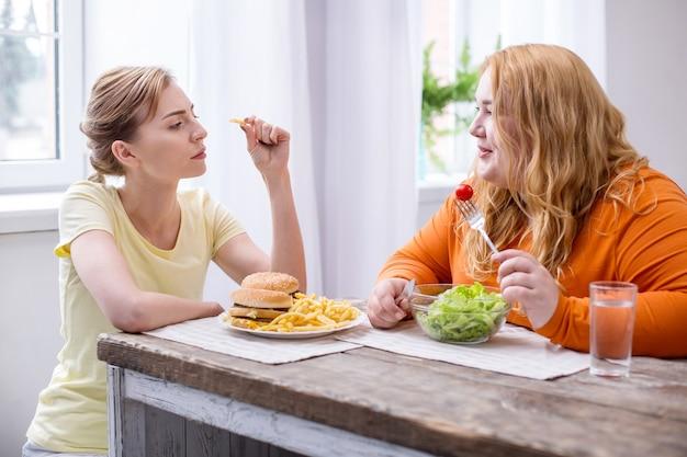 Przyjazna rozmowa. radosna gruba kobieta je sałatkę i rozmawia ze swoją szczupłą przyjaciółką jedzącą fast food