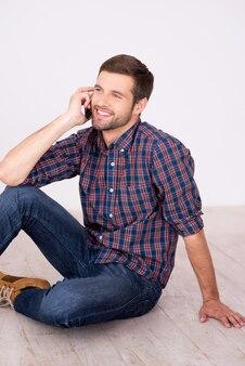 Przyjazna rozmowa. wesoły młody człowiek rozmawia przez telefon komórkowy i uśmiecha się do kamery siedząc na drewnianej podłodze