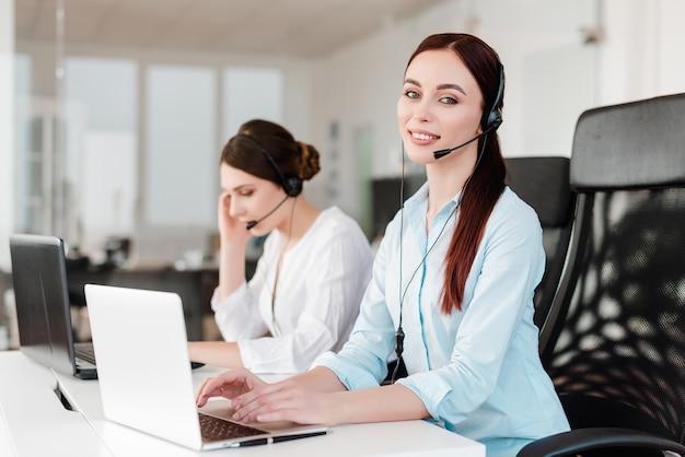 Przyjazna sekretarka rozmawia z ludźmi za pomocą zestawu słuchawkowego w biurze