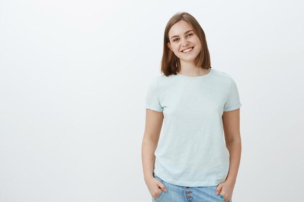Przyjazna śliczna biała dziewczyna z krótkimi fryzurami i uroczym trzepoczącym uchem, uśmiechająca się radośnie trzymając ręce w kieszeniach i wpatrująca się z radosnym, zabawnym spojrzeniem pozująca na białej ścianie