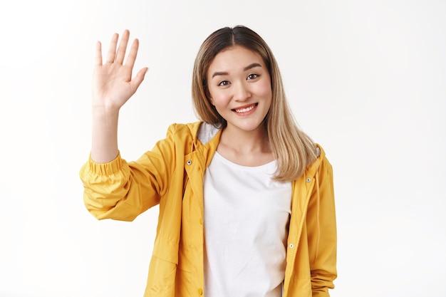 Przyjazna słodka wesoła wychodząca azjatycka blond dziewczyna podniosła rękę do góry piątka chcę się przywitać powitanie radośnie uśmiechnięty szeroko ząbkowany pozytywny uśmiech powitanie członków zespołu przedstawia się