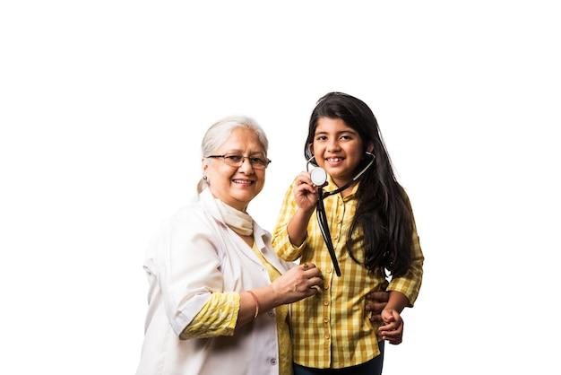 Przyjazna starsza indyjska azjatycka lekarka pediatryczna z uroczą małą dziewczynką pacjentką, na białym tle nad białym