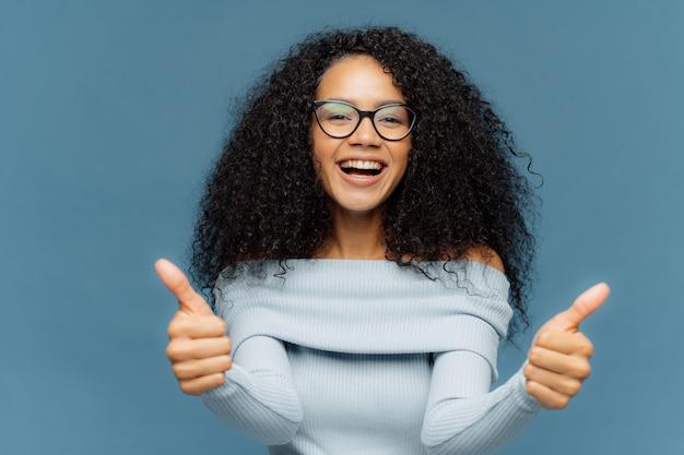 Przyjazna szczęśliwa afroamerykanka coś poleca i wyraża aprobatę