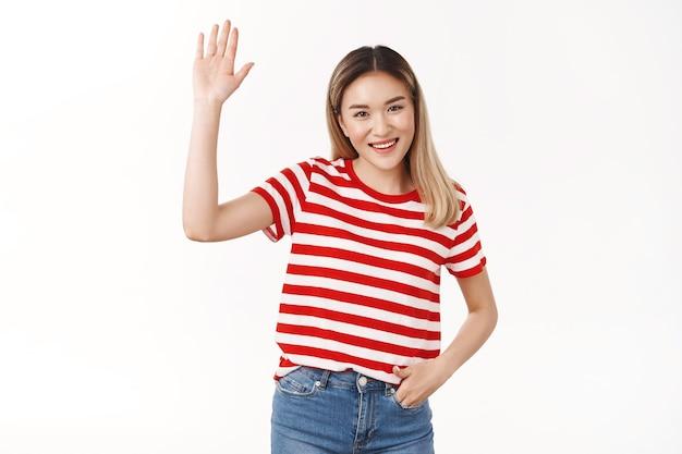 Przyjazna towarzyska towarzyska ładna azjatycka blond dziewczyna podnosi rękę machając dłonią cześć cześć gest uśmiechnięta szeroko szczęśliwa przedstawia się nowym członkom, stojąca biała ściana