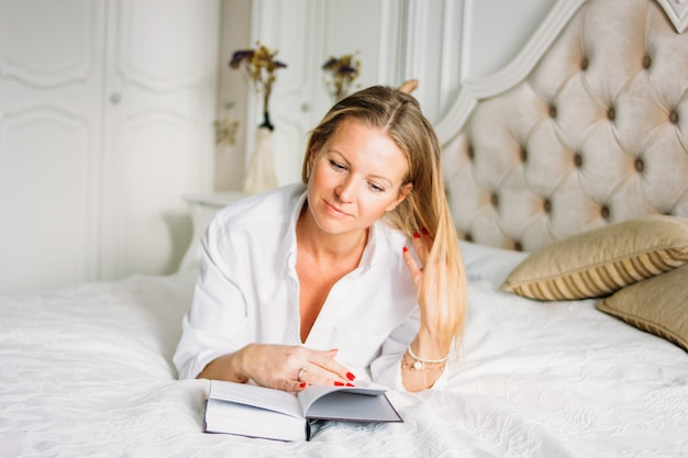 Przyjazna urocza blondynka o długich jasnych włosach w swobodnej odzieży czytająca książkę na łóżku w jasnym, bogatym wnętrzu