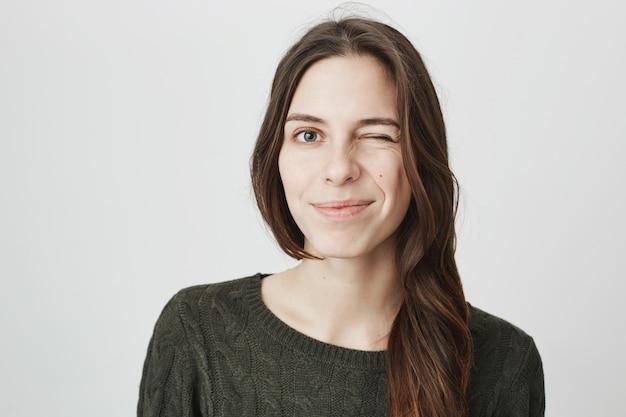 Przyjazna uśmiechnięta kobieta mruga zachęcająco