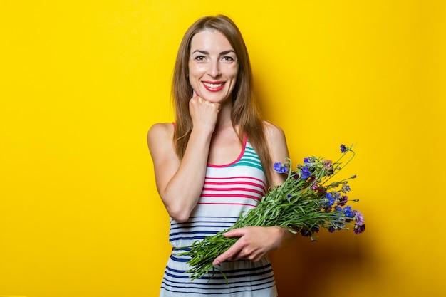 Przyjazna uśmiechnięta młoda dziewczyna w pasiastej sukience trzyma kwiaty