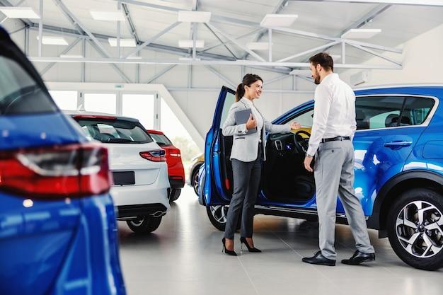 Przyjazna, uśmiechnięta sprzedawczyni pokazująca klientowi nowy samochód, stojąc w salonie samochodowym