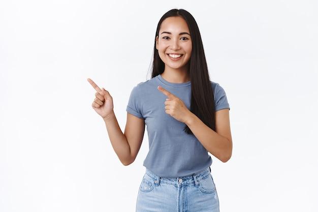 Przyjazna, uśmiechnięta szczęśliwa azjatka doradza gdzie znaleźć co potrzeba, wskazuje palcem w lewo, beztrosko uśmiechając się, poleca reklamę, promuje produkt, dyskutuje o nowym sklepie, biała ściana