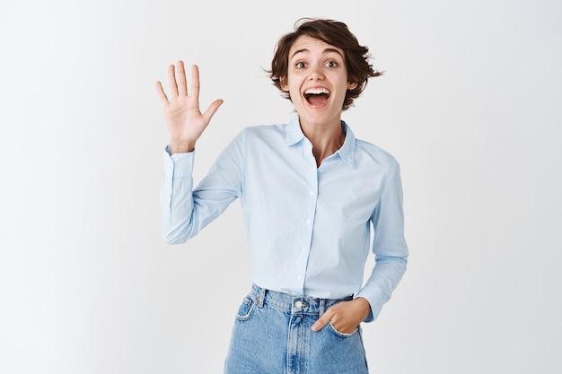 Przyjazna wesoła dziewczyna wita się, podnosząc rękę i macha w geście powitania, uśmiechając się optymistycznie, stojąc na białej ścianie