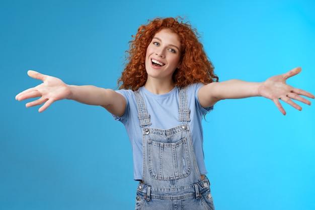Przyjazna, wesoła, rodzinna, stylowa, urocza rudowłosa kędzierzawa dziewczyna rozciąga ramiona, chce się przytulić, uśmiechnięta, delikatna, pochylona głowa, uśmiech, zapraszająca dziewczyna, ciepłe uściski stoją na niebieskim tle.