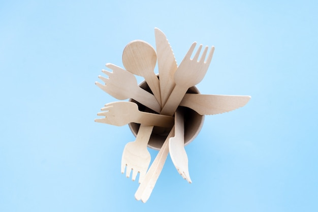 Przyjazne dla środowiska jednorazowe przybory kuchenne na niebieskim tle. drewniane widelce i łyżki w papierowym kubku. ekologia, koncepcja zero odpadów. widok z góry. leżał płasko