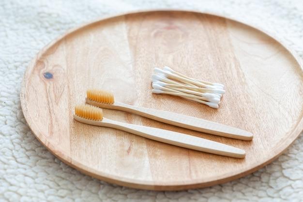 Przyjazne dla środowiska waciki bambusowe i bawełniane na różowym tle bambusowe szczoteczki do zębów dla