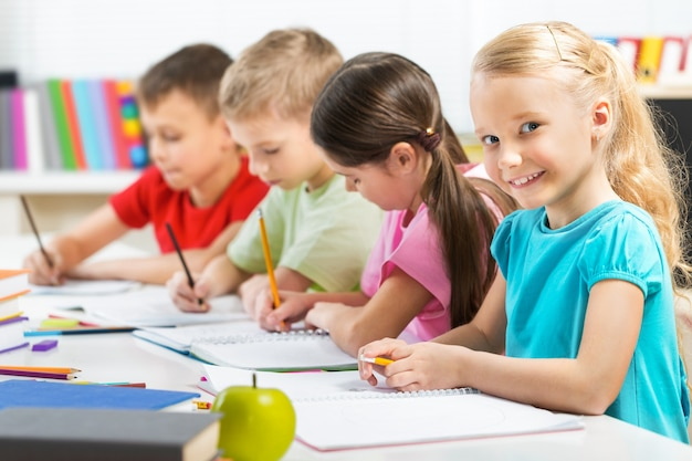 Przyjazne dzieci w wieku szkolnym na rozmytym tle w klasie