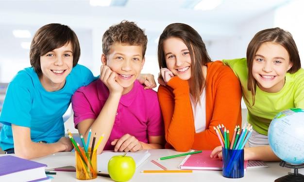 Przyjazne dzieci w wieku szkolnym studiujące koncepcję - na białym tle