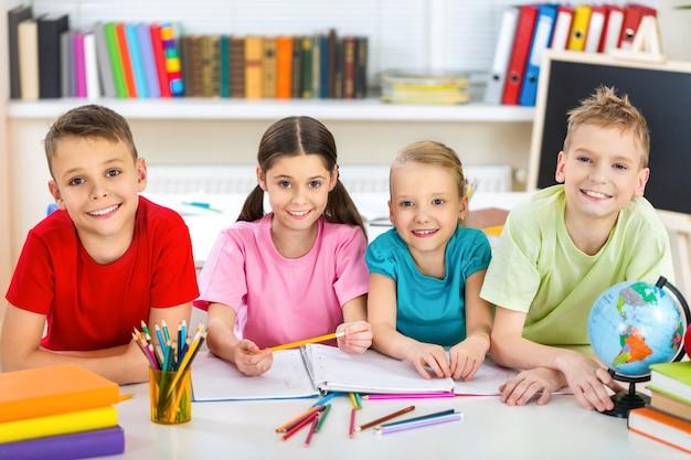 Przyjazne dzieci w wieku szkolnym z książkami na zajęciach