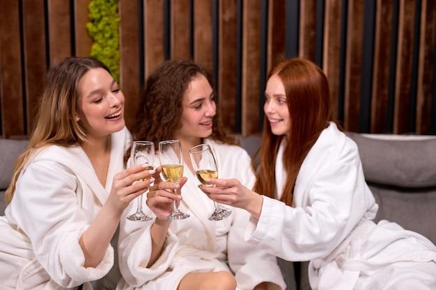 Przyjazne kobiety relaksujące się w spa i centrum odnowy biologicznej, rozmawiające i pijące razem szampana