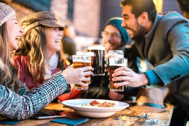 Przyjaźni faceci podchodzą do szczęśliwych dziewcząt w pubie browaru na świeżym powietrzu w okresie zimowym - selektywne skupienie się na okularach