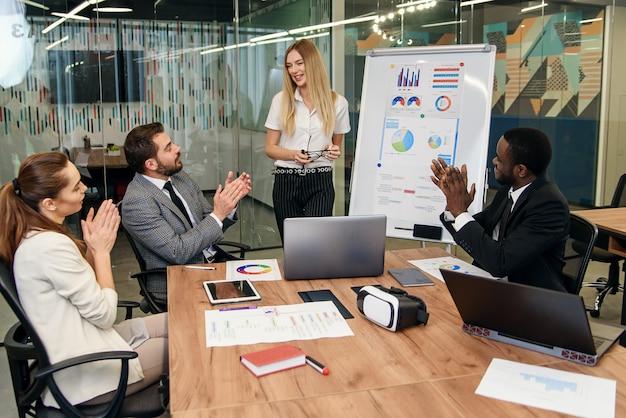 Przyjaźni koledzy omawiają swój wspólny biznes plan w ciągu dnia roboczego.