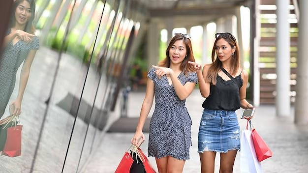 Przyjaźni żeński odprowadzenie z torba na zakupy, zakupy pojęcie.