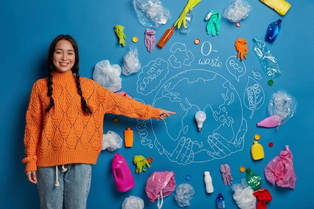 Przyjaźnie wyglądająca koreanka wskazuje przy żarówce, prosi o zebranie śmieci i ograniczenie używania plastikowych przedmiotów, zaangażowana w akcję porządkową, dba o środowisko