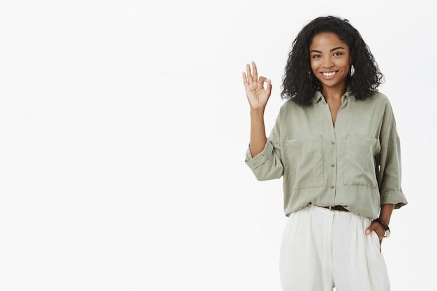 Przyjaźnie wyglądająca, radosna i pewna siebie afroamerykanka z kręconą fryzurą, pokazująca ok