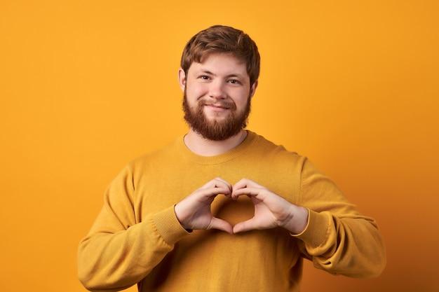 Przyjaznie wyglądający brodacz kształtuje gest serca, wysyła miłość, dobroczynność i wolontariat