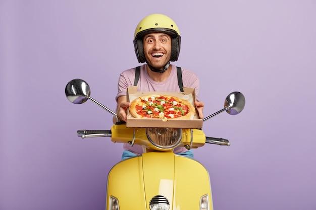 Przyjaźnie wyglądający kurier prowadzący żółtą hulajnogę, trzymając pudełko po pizzy