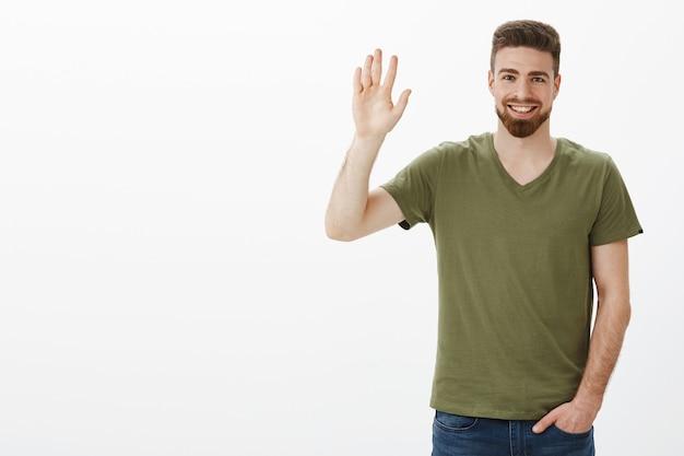 Przyjaźnie wyglądający, uroczy, brodaty chłopak czuje się nieśmiały, macha z podniesioną ręką w geście `` cześć '' lub `` cześć '', swobodnie trzyma rękę w kieszeni podczas poznawania nowych ludzi, wita na białej ścianie