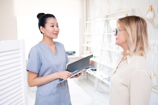 Przyjazny azjatycki kosmetolog z notesem informującym klienta o zabiegu w gabinecie kosmetycznym